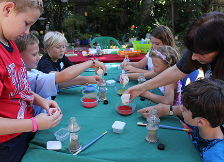 Photo of children practicing pouring colored sand